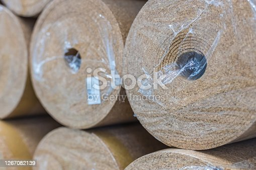 Rolls of thermal insulation from pressed brown cork in the package in stock. The concept of selling building materials on the shelves in the supermarket. Selective focus.