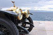 Opatija, Сroatia - June 25, 2013:  The front end of the beautiful old Rolls Royce with the hood ornament, Spirit of Ecstasy, parked on waterfront of Opatija. The ornament is in the form of a woman leaning forwards with her arms outstretched behind and above her. Billowing cloth runs from her arms to her back, resembling wings.