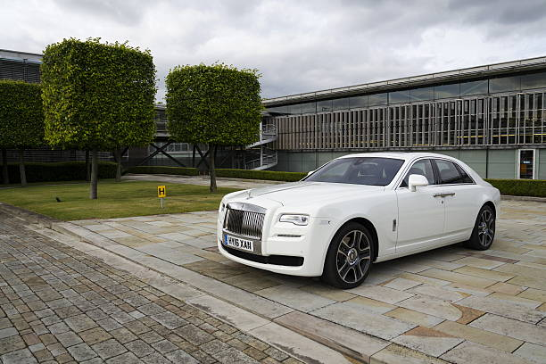 Rolls-Royce Ghost in front of the Goodwood plant Westhampnett, United Kingdom - August 11, 2016: Rolls-Royce Ghost stands in front of the Goodwood car factory. Ghost remains one of four Rolls-Royce models while company develops its first SUV. royce lake stock pictures, royalty-free photos & images