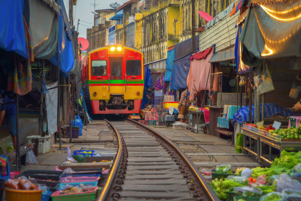Rom Hoop market. Thai Railway with a local train run through Mae Klong Market in Samut Songkhram Province, Thailand. Tourist attraction in travel and transportation concept. stock photo