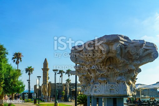 Caesarea, Israel - July 22, 2019: View of a Roma era column capital, and the Bosnian mosque, with visitors, in Caesarea National Park, Northern Israel
