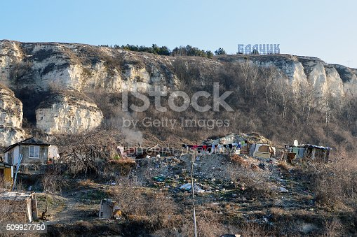 Balchik, Bulgaria – February 07, 2016: Squalid Gipsy hovels surrounded by junk right below the hill with big luminous neon sign with the name of the place - Balchik - coastal town and resort