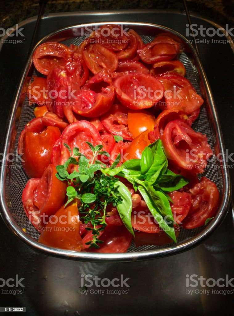 Roma tomatoes, halved and seeded, with basil, oregano and thyme. stock photo