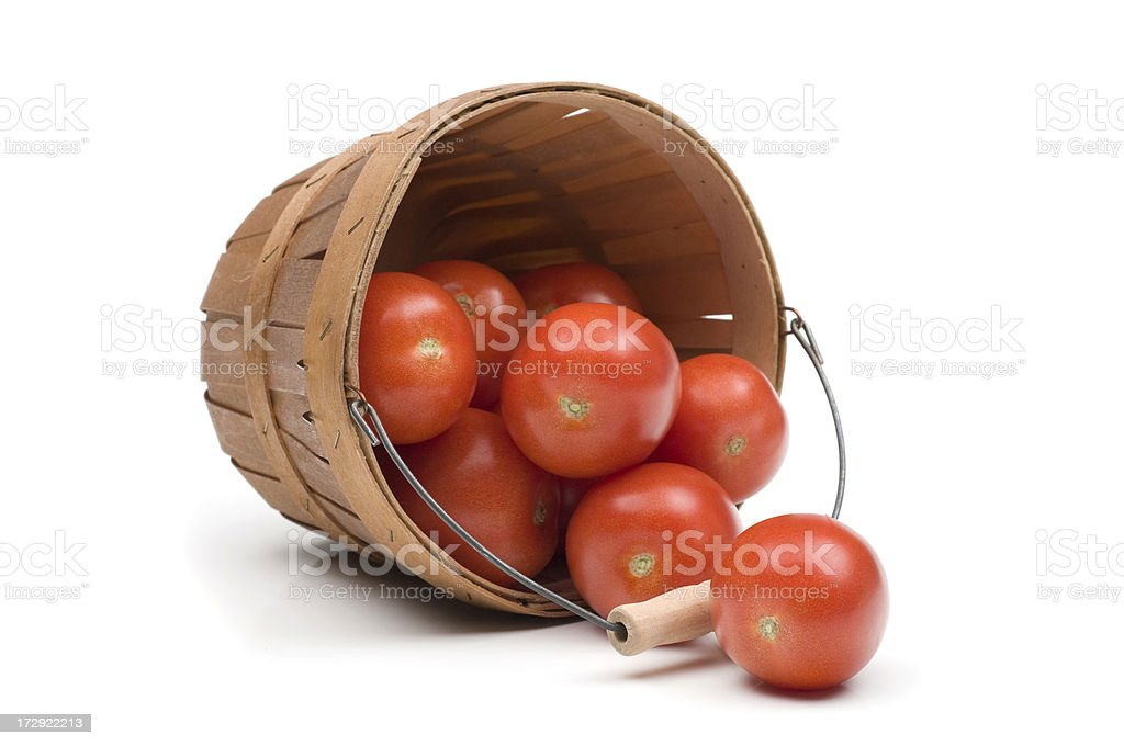 Roma tomatoes spilling from wooden basket stock photo