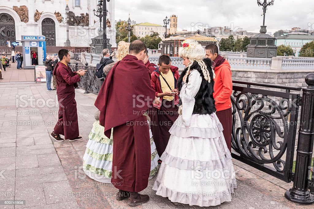 Roma women in ancient dresses make a fool of  monks stock photo