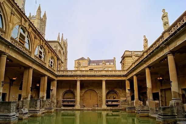 Roman Baths, Bath, England Ancient Roman Baths of Bath England at dusk  roman baths england stock pictures, royalty-free photos & images