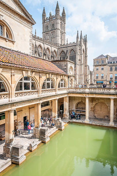 Roman Baths Bath, United Kingdom - May 17, 2013: A view of tourists walking around the main pool at the Roman Baths in Bath, England. With Bath Abbey in the background bath england stock pictures, royalty-free photos & images