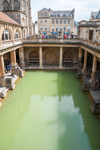 Roman Baths Bath, United Kingdom - May 17, 2013: A view of tourists walking around the main pool at the Roman Baths in Bath, England. roman baths england stock pictures, royalty-free photos & images