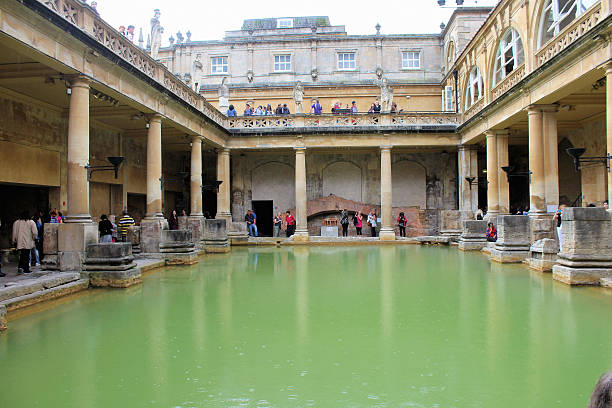 Roman Baths Bath, England - August 5, 2014: A view of the Roman Baths in Bath, Somerset, England, showing the hot springs and tourists going about their busines roman baths england stock pictures, royalty-free photos & images