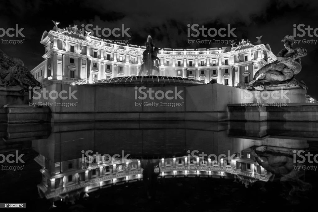 Roman building, curved around a piazza and fountain with statue and water reflection stock photo