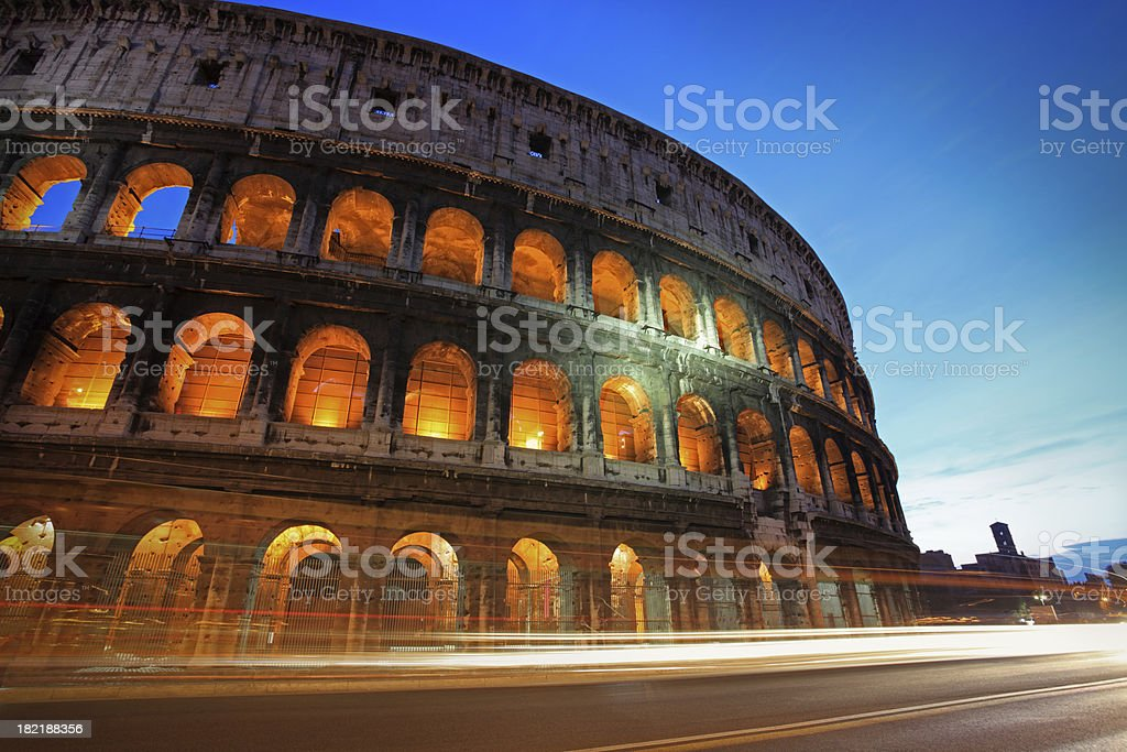 Roman coliseum at night with lights and traffic whizzing by royalty-free stock photo