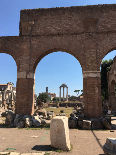 Roman Forum in Rome, Italy.  The Temple of Castor and Pollux seen through a brick arcade.  Ancient stone rubble lay around the arches. Roman Forum in Rome, Italy.  The Temple of Castor and Pollux seen through a brick arcade.  Ancient stone rubble lay around the arches. palatine hill rome stock pictures, royalty-free photos & images