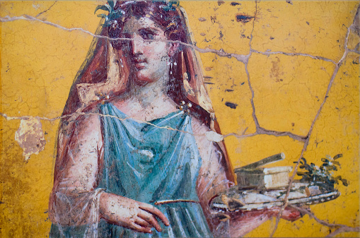 detail of the fresco in Pompeii with winged griffin on a red background Pompeian