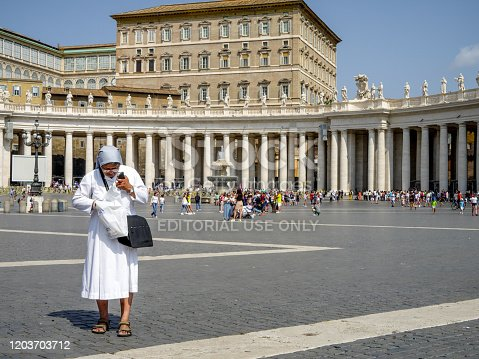 Vatican, Italy, July 06 - A roman nun walking in the St. Peter's square, one of the places most visited by millions of people every year in Rome. In the background Bernini's colonnade and the Apostolic palace.