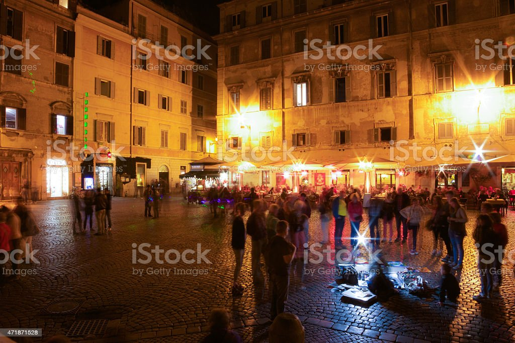 Roman Piazza and Street Performer at Night stock photo