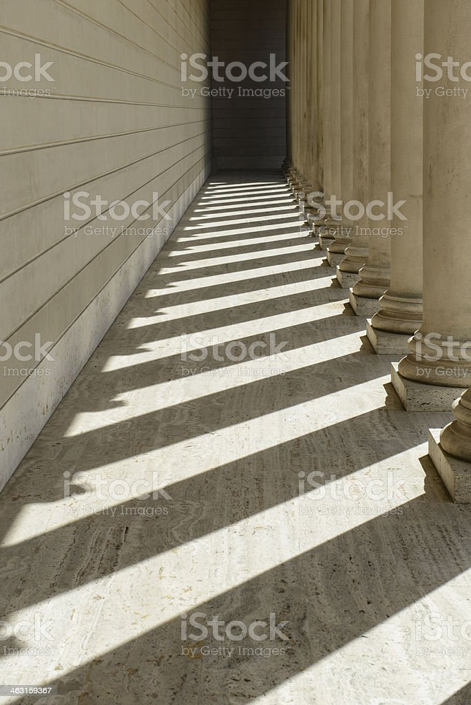 Roman pillars of education and their shadows at university stock photo