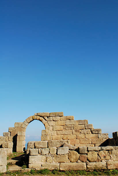 roman ruins against vibrant blue sky stock photo