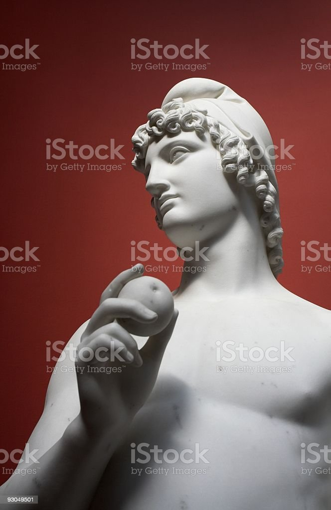 Roman statue of a young man holding an apple. stock photo