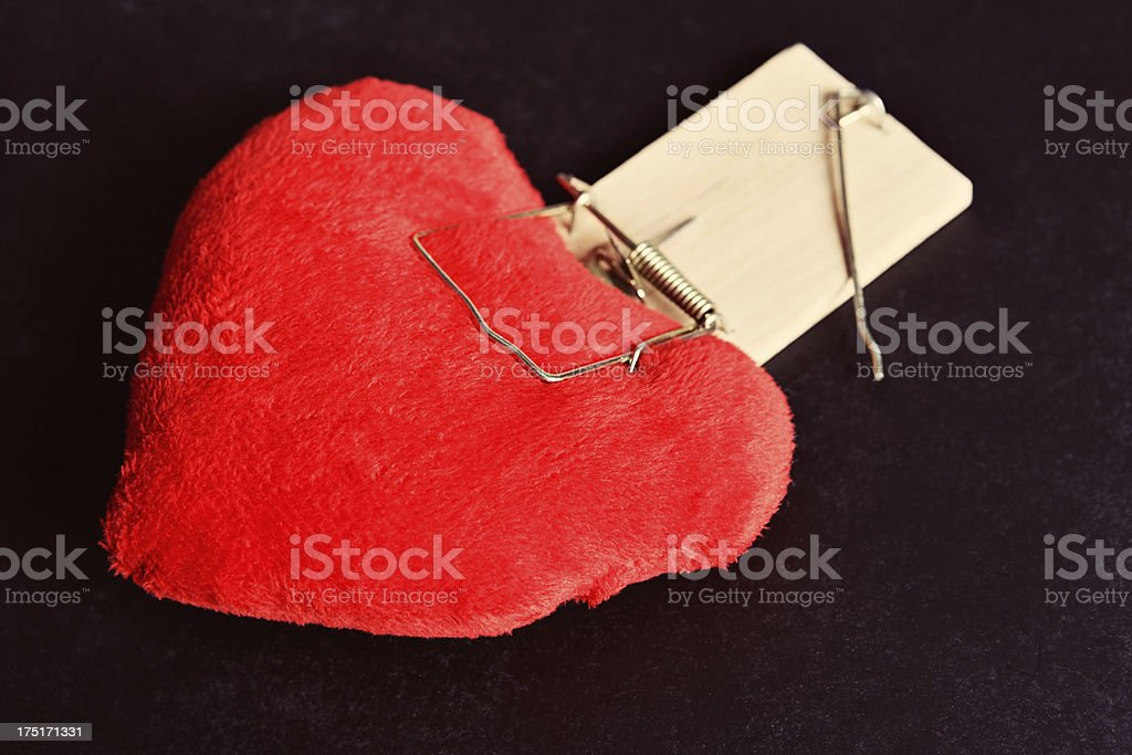 Romance can be a trap! Heart caught in mousetrap royalty-free stock photo