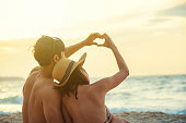 Romance couple made a heart shape together by hands on the beach at sunset. Love, wedding and valentine concept.