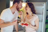 Young cheerful romantic couple is flirting in front of the open refrigerator in the kitchen feeding each other with tasty food.
