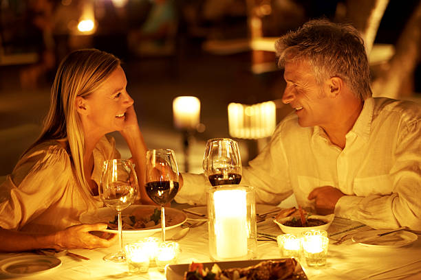 Romance in a restaurant Mature couple look into one another's eyes at a romantic candlelit dinner table for two stock pictures, royalty-free photos & images