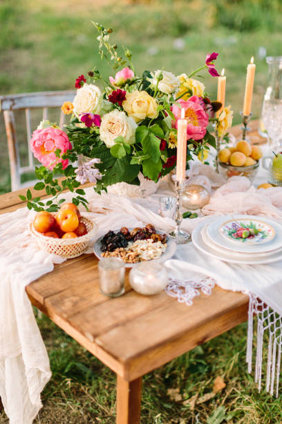 romance, love, wedding, holidays, decoration, rest concept - romantic table setting with bright multicolored bouquet in centre, white feast serveware, slender candles and fruits and nuts - foto stock