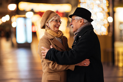 Happy elderly couple embracing each other while standing in a city street on Christmas