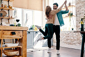 Full length of beautiful young couple in casual clothing dancing and smiling while standing in the kitchen at home