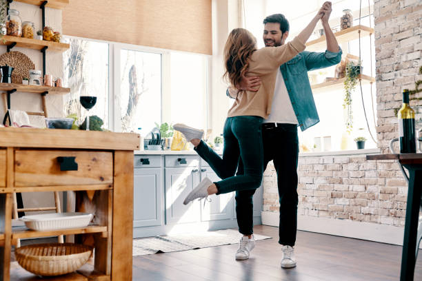 Romance. Full length of beautiful young couple in casual clothing dancing and smiling while standing in the kitchen at home dancing stock pictures, royalty-free photos & images