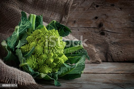 Romanesco broccoli or Roman cauliflower on a rustic wooden background with copy space, the healthy vegetable Brassica oleracea is a variation of cauliflower bred near Rome, selective focus