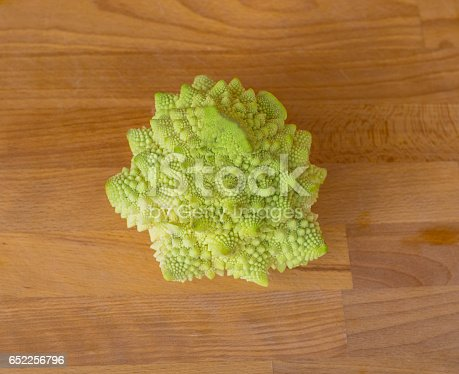 Bright green autumn cabbage romanesco on a wooden board.