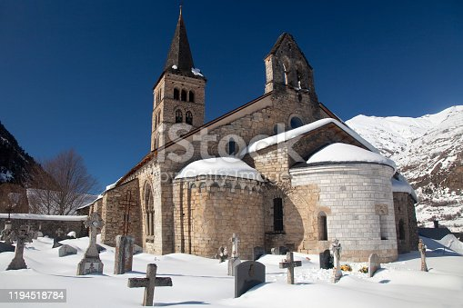 Horizontal exterior view of the Romanesque Santa María church with its apse and graveyard covered by snow, Artíes, Vall d'Aran, Lleida, Catalonia