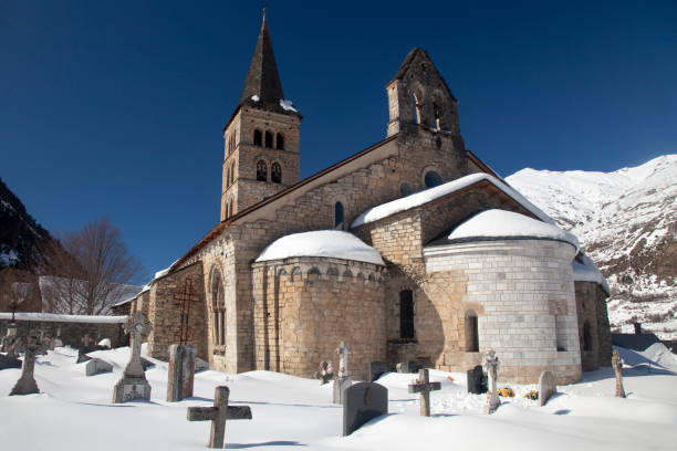Romanesque church in Val d'Aran Horizontal exterior view of the Romanesque Santa María church with its apse and graveyard covered by snow, Artíes, Vall d'Aran, Lleida, Catalonia romanesque stock pictures, royalty-free photos & images