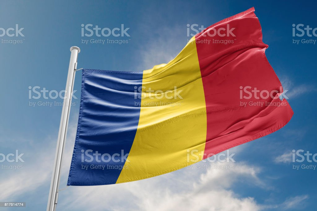 Romania Flag is Waving Against Blue Sky stock photo