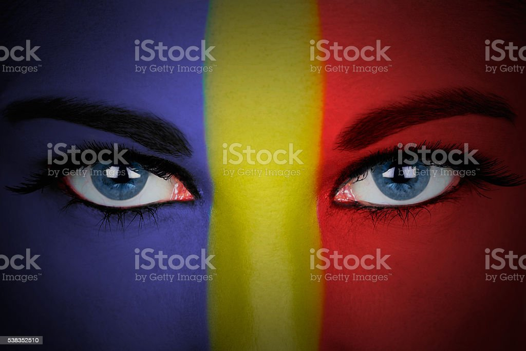 Romania flag painted on the face of a woman. stock photo