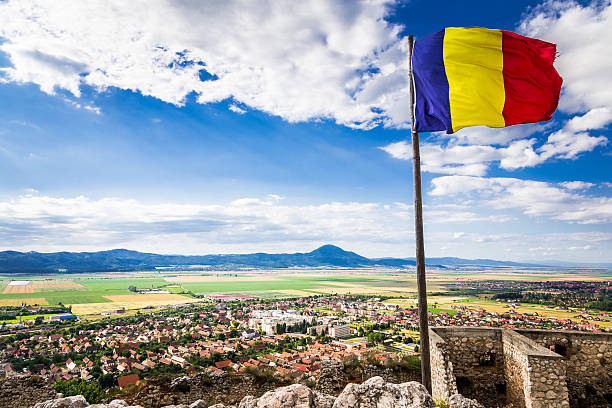 romanian flag flying above the town of rasnov, transylvania, romania - romania foto e immagini stock