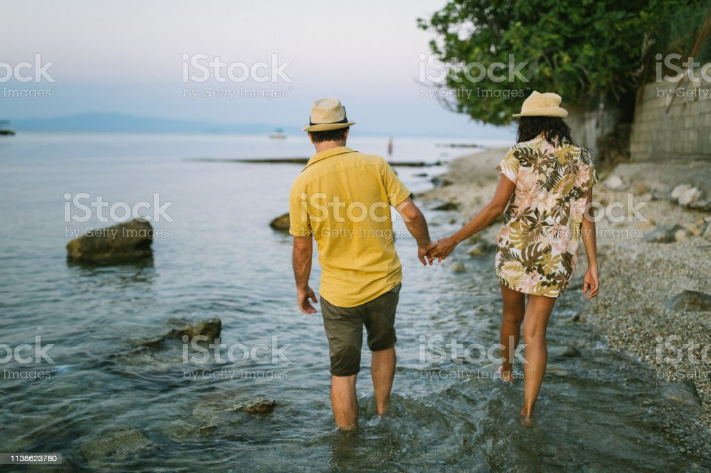 Couple holding hands on beach by the sea, walking , rear view, Greece
