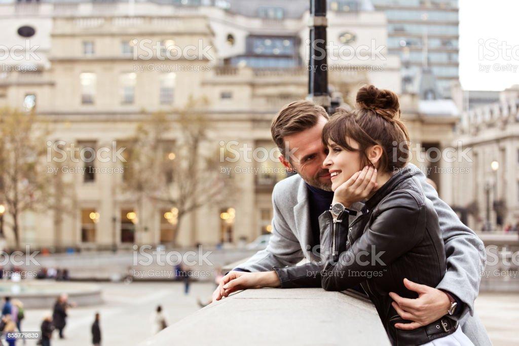 Casal adulto romântico abraçando em Trafalgar Square, a temporada de outono - foto de acervo