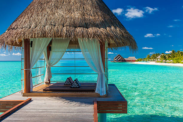 Romantic and luxurious overwater spa with tropical lagoon view Romantic and luxurious overwater spa with panoramic tropical lagoon view bungalow stock pictures, royalty-free photos & images
