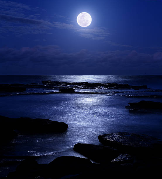 Romantic and serene moonrise over the Pacific Ocean at night stock photo