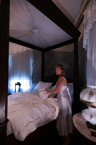 Woman in long white night gown beside a rare 1880 Mallard antique four-poster bed at T'Frere's B&B, a Cajun 1880 Acadian colonial home made of red cypress, Lafayette, Louisiana, USA