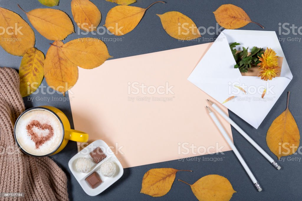 Romantic autumn mock-up. Sheet of beige paper, white envelope with note and flower, yellow and orange leaves, pencils, cup of cappuccino with heart on foam and candies.Top view. stock photo