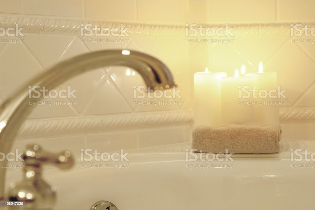 Romantic bath with candles lit in a blurred warm background. stock photo