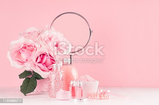 1056636898 istock photo Romantic bathroom interior in pastel pink and silver color - flowers, round mirror,  bath accessories, cosmetic products - cream, salt, rose oil, soap on white wood table. 1132685217