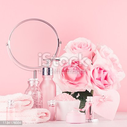 1056636898 istock photo Romantic bathroom interior in pastel pink, silver color - flowers, round mirror, bath accessories, cosmetic products - cream, salt, rose oil, soap on white wood table. 1134178334