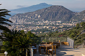 Romantic benches and a table on the terrace at Villa Cinzia in Sant'Agnello near Sorrento on the Amalfi Coast with views of the Gulf of Naples and Vesuvius. Italy