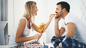 Closeup side view of a mid 20's couple sharing food in bed on a weekend morning. She's  beautiful blond woman wearing white tank top and pajamas, and she's feeding her boyfriend with cookies.