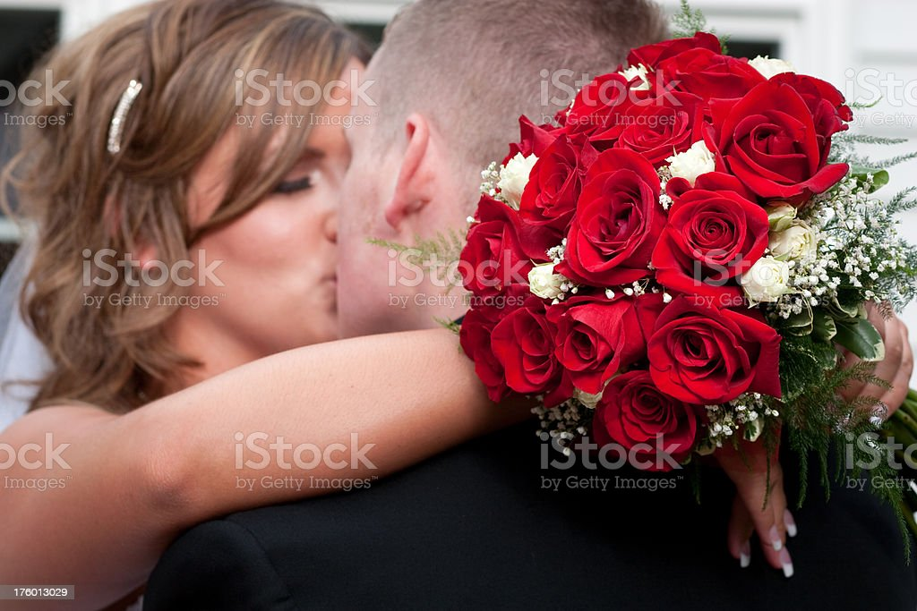 Romantic Bride and Groom Kissing Holding Wedding Bouquet Red Roses royalty-free stock photo