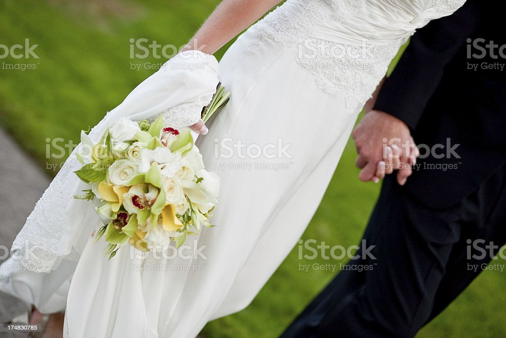 Romantic Bride and Groom Walking Holding Hands with Bridal Bouquet royalty-free stock photo